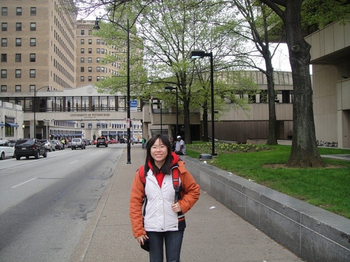 University of Pittsburgh in the background. At one of the bus stops where there are no shelters, and the only indication of the bus stop was the blue sign on the post behind.