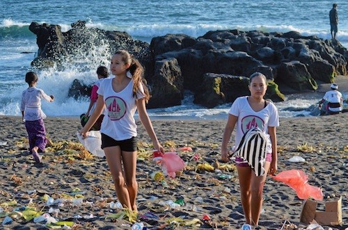 The sisters standing amidst trash on a beach in Bali (Photo credit: Bye Bye Plastic Bags)